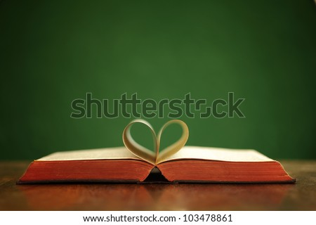 Bible on table with pages folded into heart shape - stock photo