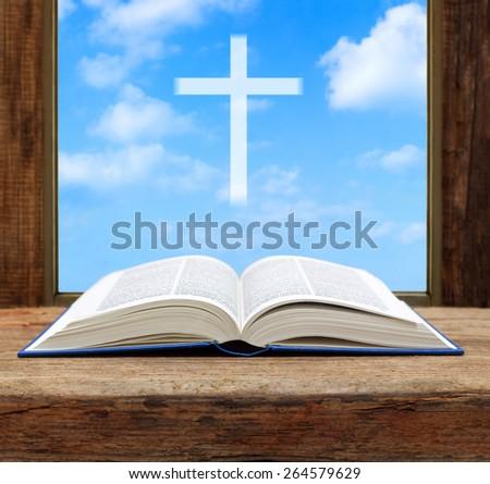 Bible open christian cross light sky view window wooden shallow DOF - stock photo