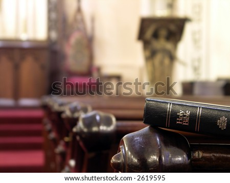 Bible resting on the back of a church pew. Shallow DOF with sharp focus on bible. - stock photo
