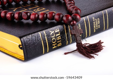 bible with a rosary on a white background