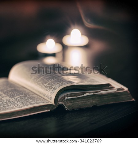 Bible with candles in the background. Low light scene.