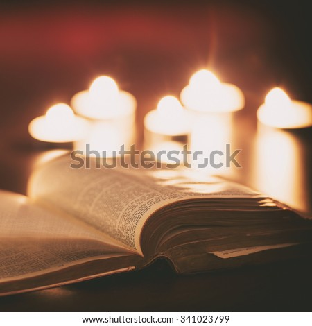 Bible with candles in the background. Low light scene. - stock photo