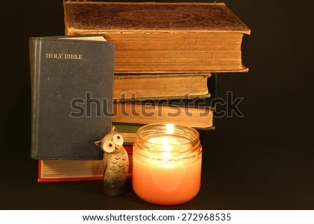 Bible with old books, candle and an owl on a black background - stock photo
