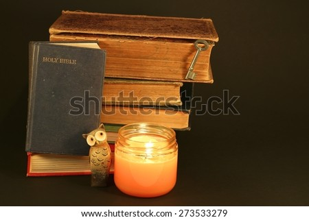 Bible with stack of old books, candle, owl and key on a black background - stock photo
