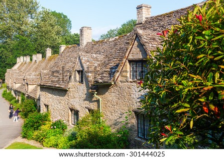 BIBURY, ENGLAND - JULY 08, 2015: Arlington Row with unidentified people in Bibury.  Bibury is a main destination for tourists visiting traditional rural villages and ornate buildings of the Cotswolds