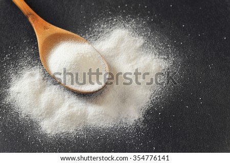 Bicarbonate in a wooden spoon on black background - stock photo