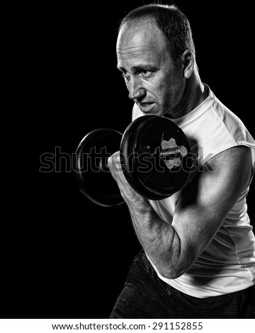 Bicep curl exercise with dumbbell. Studio shot over black. - stock photo