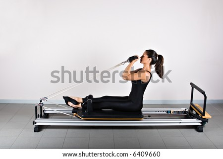 Bicep reformer position. Pilates gymnastics is a Germanic evolution of yoga, used by athletes to improve flexibility and body fitness and by chiropractors for patient recovery. - stock photo