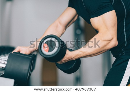 Bicep training - Muscular young man in gym. Selective focus, toned image - stock photo