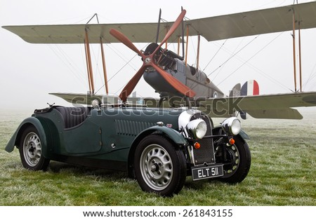 BICESTER, UK - JANUARY 4: A vintage Morgan sportscar and WW1 Be2e biplane are displayed at the Bicester Heritage site as part of the Sunday Brunch and Icicle run event on January 4, 2015 in Bicester - stock photo