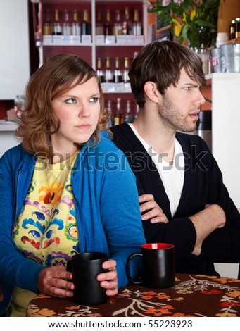 Bickering and frustrated couple sitting with coffee at a table - stock photo