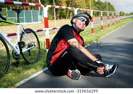 Bicycle accident. Biker holding his ankle. - stock photo