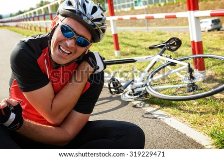 Bicycle accident. Biker holding his shoulder. - stock photo