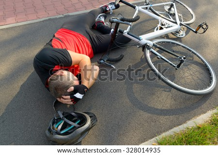 Bicycle accident. Biker lying on the road and holding his head - stock photo
