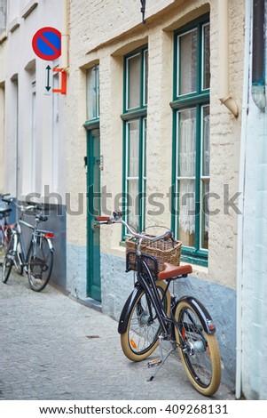 Bicycle against brick wall in Brugge, Belgium - stock photo