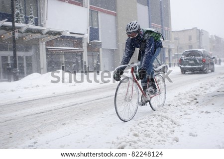 Bicycle courier in winter snow storm - stock photo