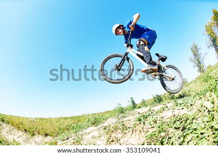 Bicycle extreme sport jump. Young cyclist high jumping downhill on the mountain bike cross-country - stock photo