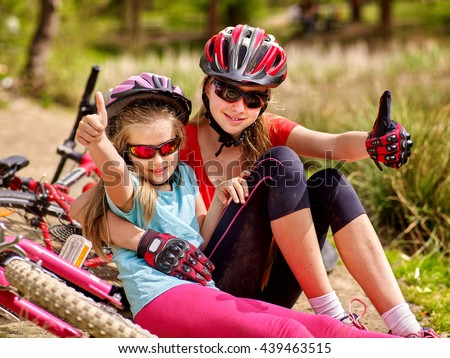 Bicycle family. Happy mother and daughter are sitting on road near bicycle and show thumb up. Bicycle racing concept. - stock photo