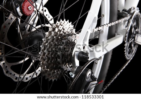 Bicycle gears, disc brake and rear derailleur. Studio shot on black background - stock photo