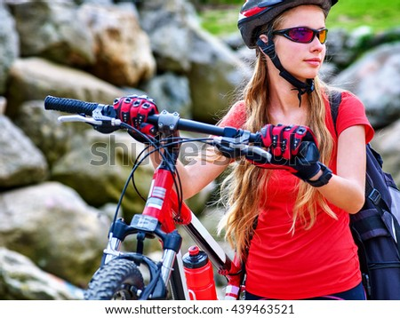 Bicycle girl. Girl rides bicycle into mountains. Girl on bicycle in mountaineering . Girl carries her bike over rocks. Bicycle travel. - stock photo
