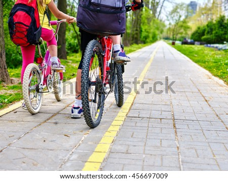 Bicycle girl. Legs of bicycle girl . Girls children cycling on yellow bike lane. Bike share program save money and time at city street. Back view. Bicycle sport concept. - stock photo
