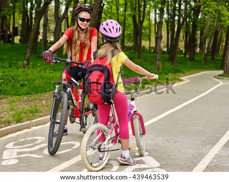 Bicycle girl wearing bicycle helmet and glass with rucksack ciclyng bicycle. Girls children cycling meet on white bike lane. Bicycle travel. - stock photo