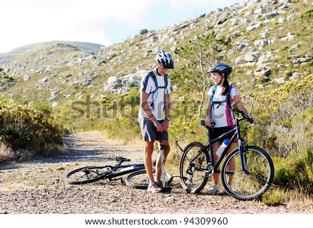 Bicycle has flat tyre and man helps his girlfriend pump it up. outdoors mountain bike couple. - stock photo