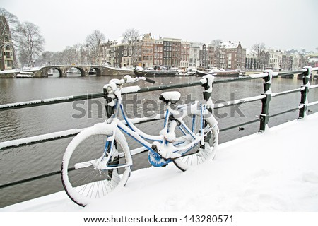 Bicycle in Amsterdam the Netherlands covered in snow - stock photo