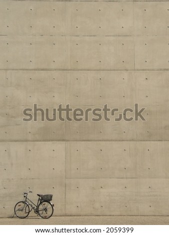 Bicycle in front of concrete wall - stock photo