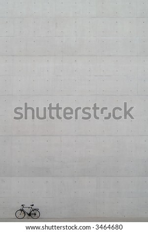 bicycle in front of huge fair faced concrete wall - stock photo