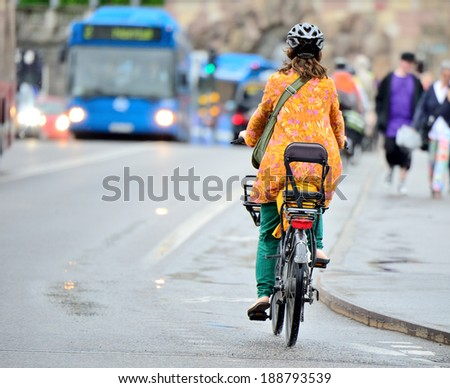 Bicycle in light summer rain in traffic - stock photo