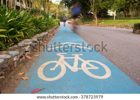 Bicycle lane signage on blue street - stock photo