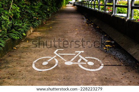 Bicycle lane with white bicycle sign riverside - stock photo