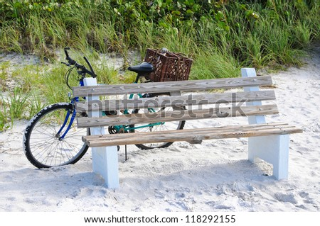 Bicycle Leaning against a Wooden Bench on the Beach - stock photo
