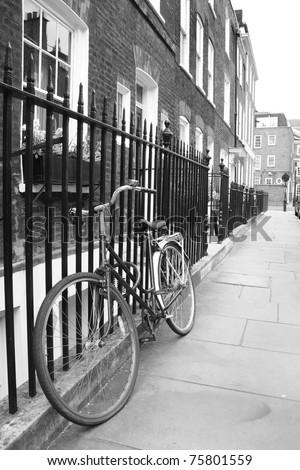 Bicycle leaning against railings in a London street - stock photo