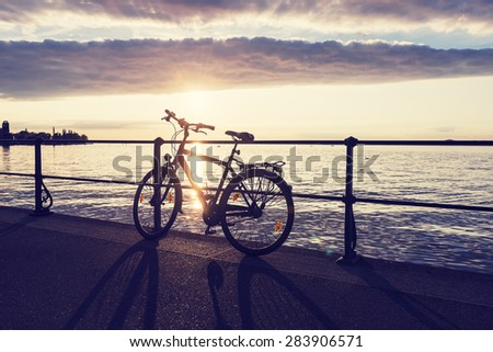 Bicycle leaning on the railing on the waterfront of Lake Constance. Bodensee. - stock photo