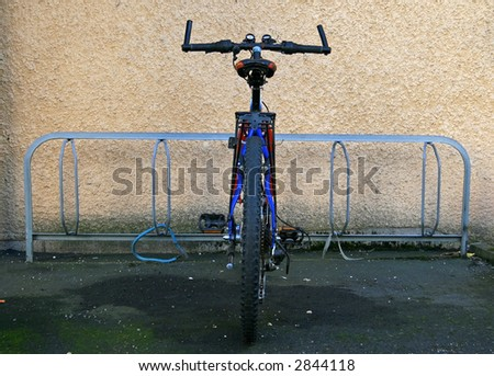 Bicycle locked by the stand - stock photo