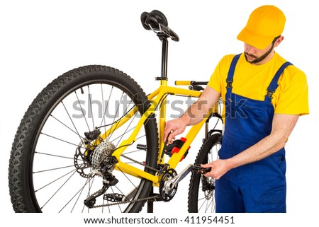 bicycle mechanic adjusting front derailleur mechanism on mountain bike - stock photo