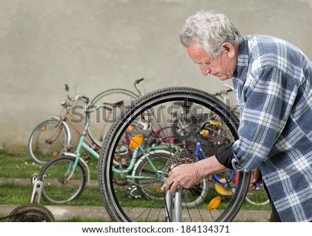 Bicycle mechanic repairing bicycle wheel in courtyard - stock photo