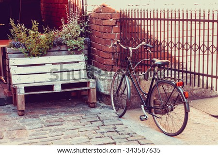 Bicycle near outdoors cafe on old street. Selective focus. Vintage styled. - stock photo