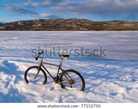Bicycle on ice surface of huge frozen Lake Laberge, Yukon Territory, Canada, in April. - stock photo