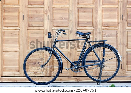 Bicycle on vintage wooden house wall - stock photo