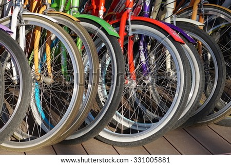 Bicycle Parking in the Park. Rent bikes in the summer. Wheel detai of a group of bikes. - stock photo