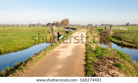 Bicycle path and ditches in the foreground and three windmills in the background of a landscpae in a polder area in the Netherlands. - stock photo