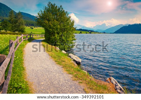 Bicycle path around Muta (Haidersee) lake in the Italian Alps. Colorful summer morning on the Reschensee lake. Place is located near the village St. Valentin, Alps, Italy, Europe. - stock photo
