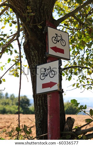 Bicycle path signpost with two arrows pointing different ways - stock photo