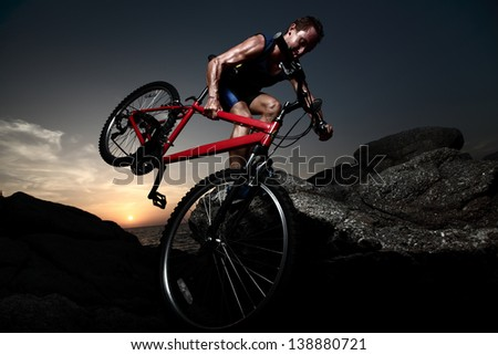 Bicycle rider crossing rocky terrain at sunset - stock photo