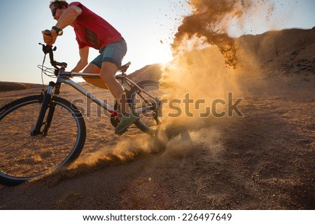 Bicycle rider moving on the desert with lot of dust