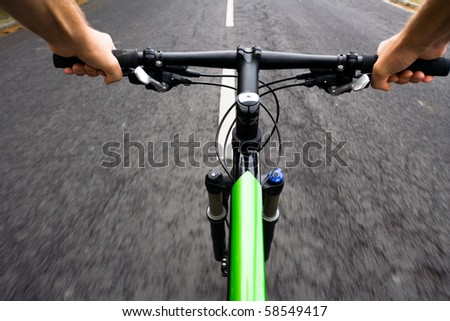 Bicycle rider riding real fast on mountain bike, motion blur - stock photo