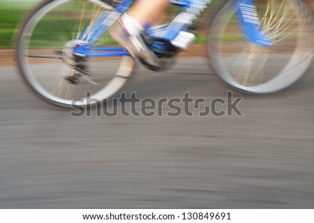 Bicycle riding on country road, motion blur. - stock photo
